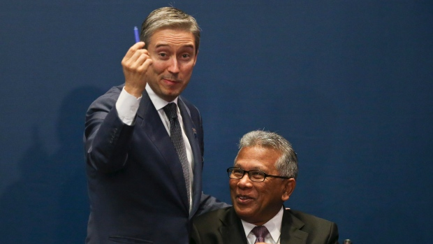 Canada's Minister of International Trade Francois-Philippe Champagne, left, and the Minister of International Trade and Industry of Malaysia Y.Bhg. Datuk J. Jayasiri, joke during the signing ceremony of the Comprehensive and Progressive Agreement for Trans-Pacific Partnership in Santiago, Chile, Thursday, March 8, 2018. (Esteban Felix/AP Photo)
