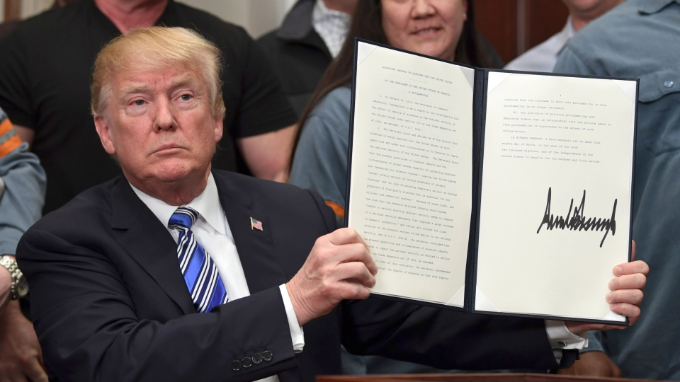 U.S. President Donald Trump holds up a proclamation on aluminum during an event in the Roosevelt Room of the White House in Washington, Thursday, March 8, 2018. He also signed one for steel. (AP Photo/Susan Walsh)