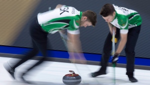 Saskatchewan second Kirk Muyres, left, and lead Dallan Muyres sweep a rock as they play Manitoba at the Tim Hortons Brier curling championship at the Brandt Centre in Regina on Sunday, March 4, 2018. (Andrew Vaughan / The Canadian Press)