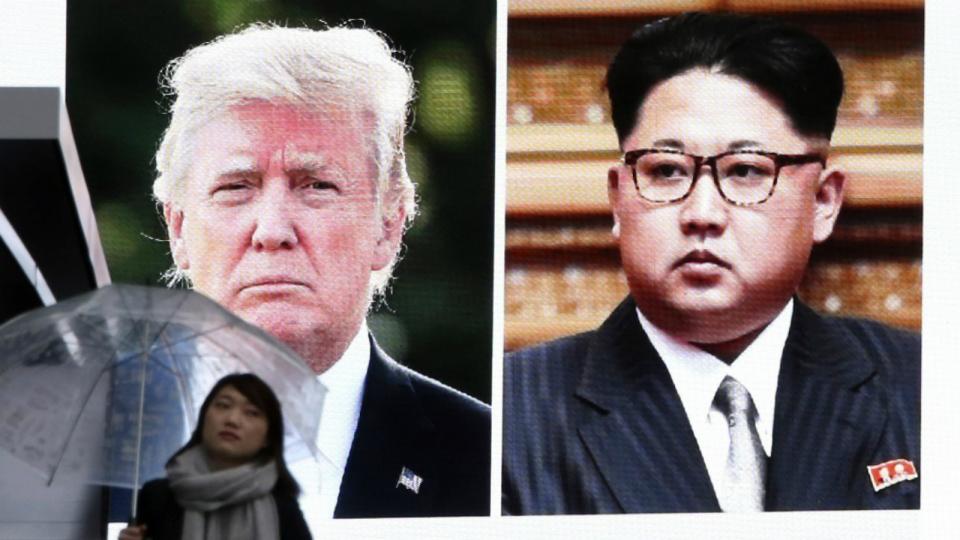 A woman walks by a huge screen showing U.S. President Donald Trump, left, and North Korea's leader Kim Jong Un, in Tokyo, Friday, March 9, 2018. (AP Photo/Koji Sasahara)