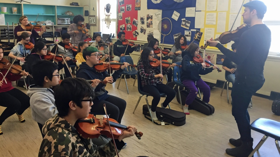 Juno Award-winning fiddler Karrnnel Sawitsky, from Saskatoon, helps students at St. Michael Community School write and compose a song. (Ashley Field/CTV Saskatoon)