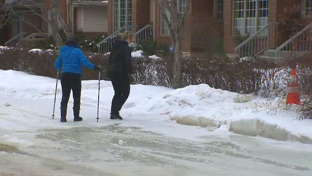 Cloverdale residents Susan Yackulic and Bambi Barnes try to negotiate ice on the sidewalk in their river valley neighbourhood.