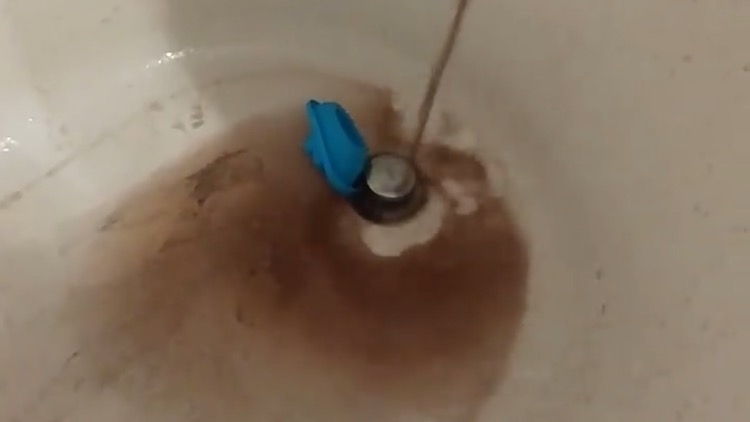 Dark brown water pours into Maria Classen's tub.