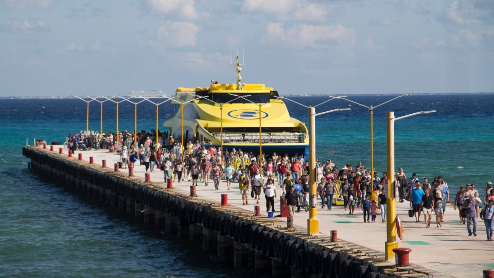 In this Friday, March 2, 2018 photo, tourists and passengers disembark from a ferry on to the wharf on Playa del Carmen, Mexico. (Gabriel Alcocer/AP Photo)