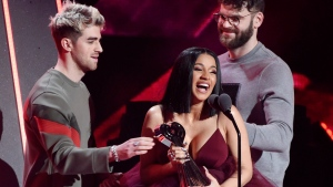 Singer Cardi B accepts the Best New Artist award from Andrew Taggart, left, and Alex Pall of The Chainsmokers during the 2018 iHeartRadio Music Awards at The Forum on Sunday, March 11, 2018, in Inglewood, Calif. (Photo by Chris Pizzello/Invision/AP)