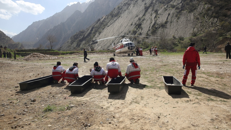 In this photo provided by the Iranian Labor News Agency, ILNA, rescue workers wait for the bodies of passengers from a Turkish private jet that crashed on Sunday in the Zagros Mountains, outside of the city of Shahr-e Kord, outside of the city of Shahr-e Kord, some 370 kilometers, or 230 miles, south of the capital, Tehran, Iran, Monday, March 12, 2018. (Mostafa Safari/ILNA, via AP)