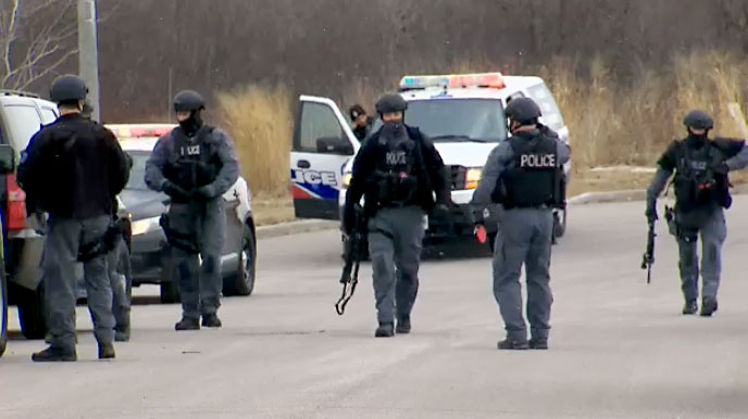 Heavily armed police officers search an area off the side of Highway 401 in Ajax after three robbery suspects abandoned a vehicle and fled into a wooded area on March 12, 2018.