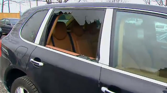 A damaged vehicle sits in an Oakville dealership lot. The owner says numerous vehicles were damaged during a break-in.