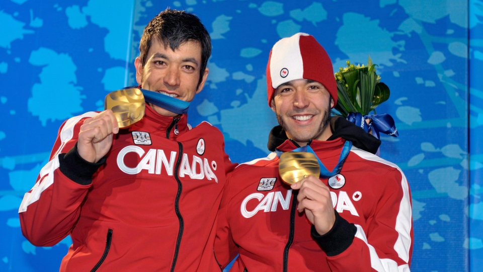 Canada's Brian McKeever, right, with his guide and brother Robin McKeever celebrate gold medals at the 2010 Vancouver Winter Paralympics. (THE CANADIAN PRESS/AP/KEYSTONE/Dominic Favre)