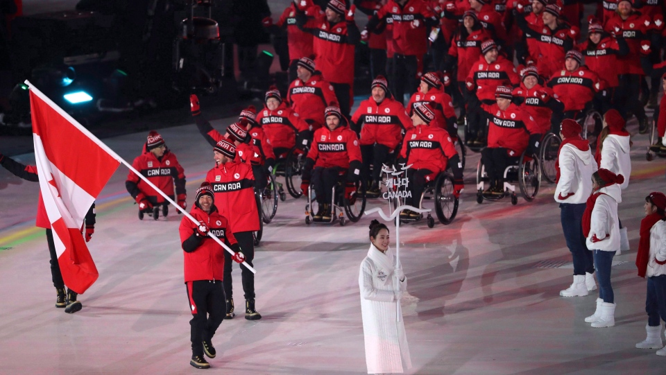 Brian McKeever carries the flag of Canada as he leads his teammates into the opening ceremony of the 2018 Winter Paralympics in Pyeongchang, South Korea, Friday, March 9, 2018.THE CANADIAN PRESS/AP/Ng Han Guan
