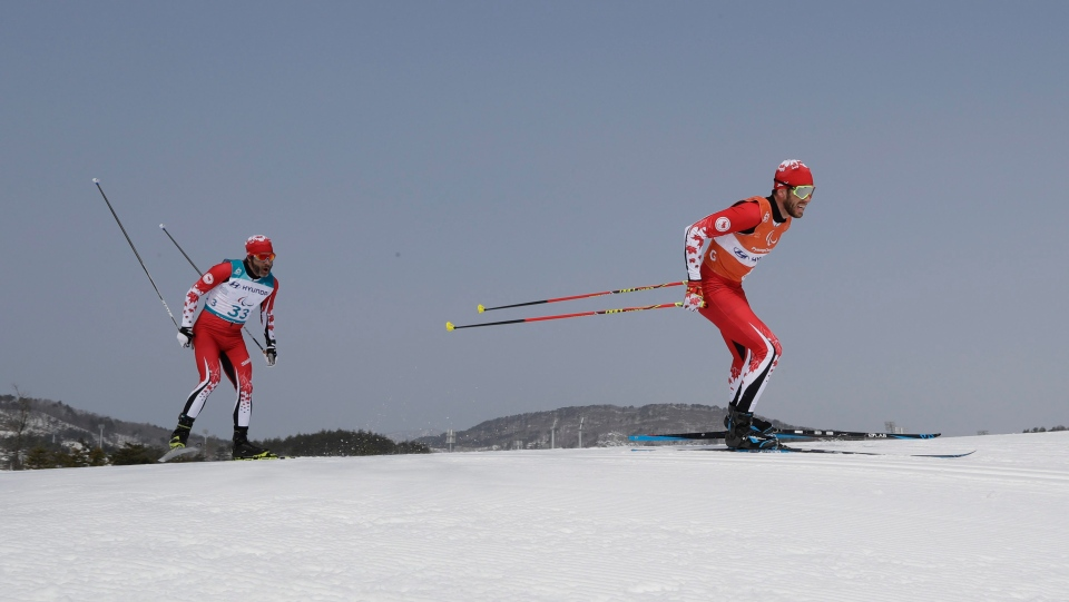 Canada's Brian Mckeever, left, and guide Graham Nishikawa compete on their way to win the gold in the men's 20km free, visually impaired, cross-country skiing at the 2018 Winter Paralympics in Pyeongchang, South Korea, Monday, March 12, 2018. (AP Photo/Lee Jin-man)