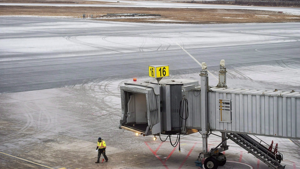 Airlines have already cancelled flights ahead of an intense winter storm that's expected to bring heavy snow, high winds and pounding surf to Atlantic Canada. A worker walks on the tarmac at the Halifax Stanfield International Airport, where most flights were cancelled, in Halifax on Thursday, Jan. 4, 2018. (THE CANADIAN PRESS/Andrew Vaughan)
