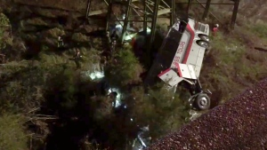 This photo provided by Jesus Tejada shows first responders searching around a bus that plunged into a ravine, Tuesday, March 13, 2018 on Interstate 10, Loxley, Ala.  (Jesus Tejada via AP)