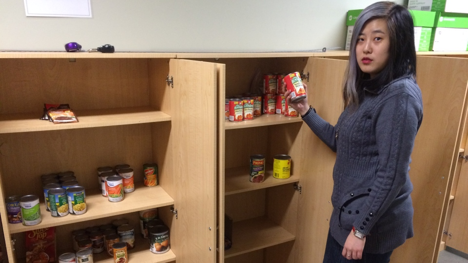 University of Windsor volunteer Angela Zhu shows the empty cupboards at the student food bank on March 13, 2018. (Michelle Maluske / CTV Windsor)