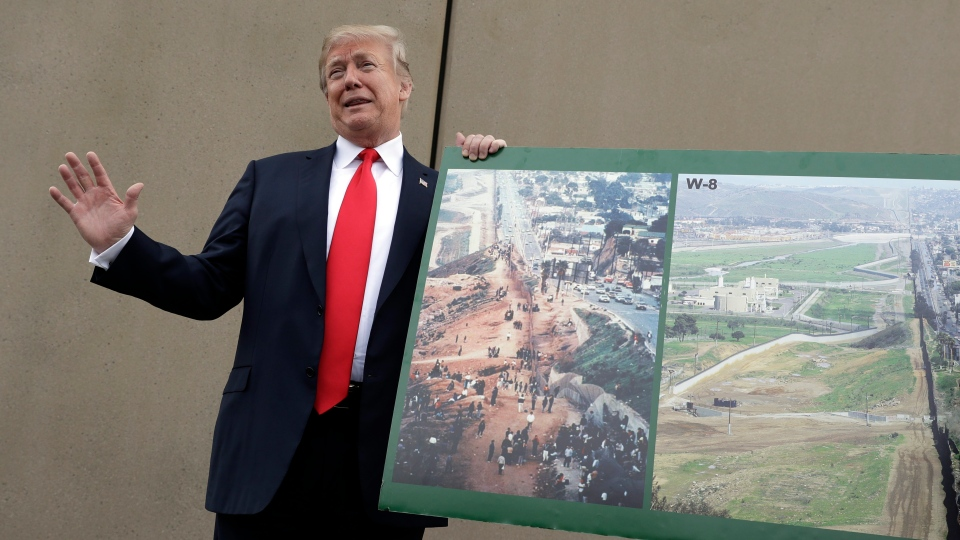 U.S. President Donald Trump holds a photo of the border area as he reviews border wall prototypes, Tuesday, March 13, 2018, in San Diego. (AP Photo/Evan Vucci)