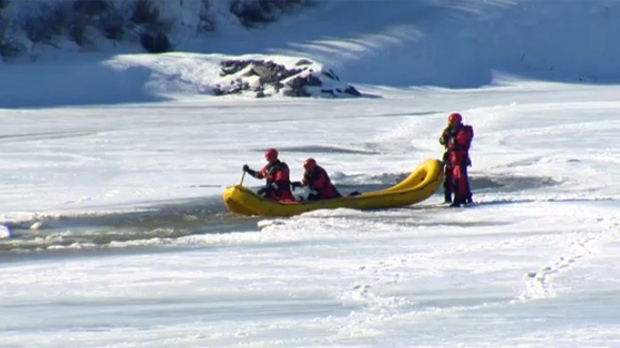 Members of the Calgary Fire Department aquatics team scour the Bow River near Shouldice Athletic Park on Tuesday afternoon for a dog that fell through the ice
