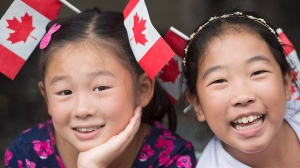 Two girls smile as they watch the annual Canada Day parade in Montreal, Saturday, July 1, 2017. (THE CANADIAN PRESS/Graham Hughes)