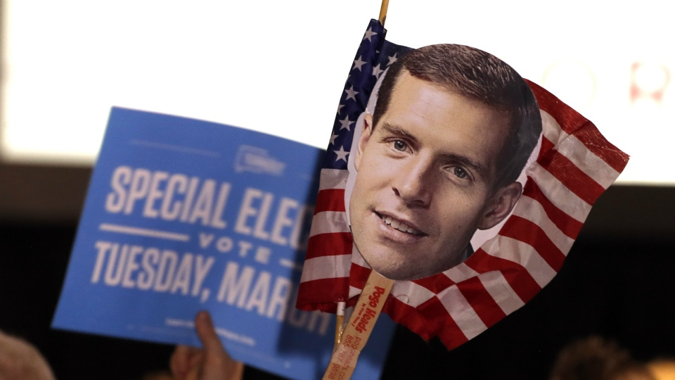 Supporters of Conor Lamb, the Democratic candidate for the March 13 special election in Pennsylvania's 18th Congressional District hold signs during his election night party in Canonsburg, Pa. on Wednesday, March 14, 2018. (AP Photo/Gene J. Puskar)