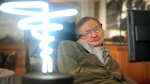 Professor Stephen Hawking poses beside a lamp titled 'black hole light' by inventor Mark Champkins, presented to him during his visit to the Science Museum in London on Feb. 25, 2012. (Anthony Devlin/PA via AP)