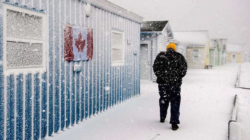 A pedestrian braves the elements on the boardwalk at Fisherman's Cove in Eastern Passage, N.S. on Tuesday, March 13, 2018. (THE CANADIAN PRESS/Andrew Vaughan)