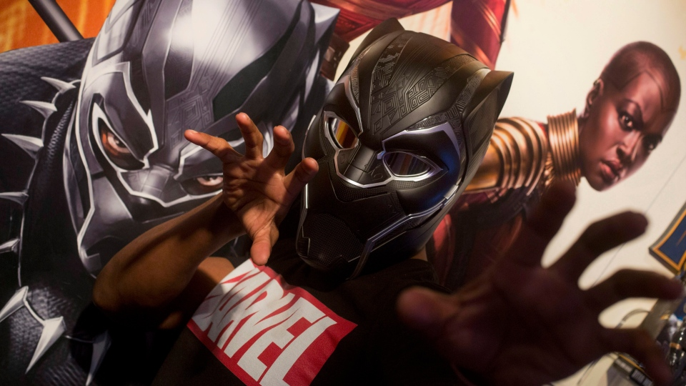 In this Tuesday, Feb. 20, 2018, photo Rafael Jordan models the Black Panther helmet from Hasbro at Toy Fair in New York. (AP Photo/Mark Lennihan)