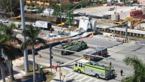 Emergency personnel responds to a collapsed pedestrian bridge connecting Florida International University Florida International on Thursday, March 15, 2018 in the Miami area. (Roberto Koltun / The Miami Herald via AP)