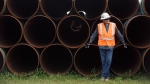 Al Beesley, Senior Safety Coordinator, leans on some pipe while waiting for a press conference to start with Alberta Premier Rachel Notley during a tour of Enbridge's Line 3 pipeline replacement project in Hardisty Alta., on Thursday, Aug.10, 2017. (Jason Franson/THE CANADIAN PRESS)