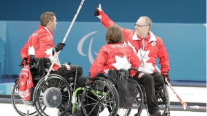 Canada's Dennis Thiessen, right, celebrates his team's victory with teammates Marie Wright, centre, and Mark Ideson, left, after the mixed wheelchair curling round robin session against Finland at the 2018 Winter Paralympics in Gangneung, South Korea, March 15, 2018. (AP Photo/Lee Jin-man)
