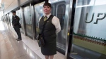 Guest Services Representative Karla Huber stands outside the Union Pearson Express train from Union Station to Pearson airport in Toronto on Wednesday, April 22, 2015. THE CANADIAN PRESS/Frank Gunn
