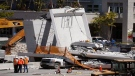 Workers stand next to a section of a collapsed pedestrian bridge, Friday, March 16, 2018 near Florida International University in the Miami area. (AP Photo/Wilfredo Lee)
