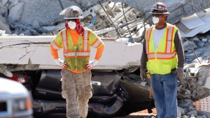 Workers stand in front of crushed cars under a section of a collapsed pedestrian bridge, Friday, March 16, 2018 near Florida International University in the Miami area. The new pedestrian bridge that was under construction collapsed onto a busy Miami highway Thursday afternoon, crushing vehicles beneath massive slabs of concrete and steel, killing and injuring several people, authorities said. (AP Photo/Wilfredo Lee)