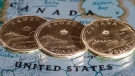 Canadian dollar coins are displayed on a map along the border of Canada and the United States of America, in Montreal in a January 9, 2014, file photo. As global stock markets have been hammered over the past week, the Canadian dollar has also been dropping alongside oil prices, but amid the current noise of volatility and falling job numbers reported Friday, some market observers still see it moving higher this year. THE CANADIAN PRESS/Paul Chiasson