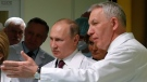 Russian President Vladimir Putin, center, listens to Yevgeny Shlyakhto, right, director general of the Almazov National Medical Center in St. Petersburg, Russia, Friday, March 16, 2018. (Anatoly Maltsev/Pool Photo via AP)