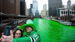 Stacey Peterson and Kevin McGuire take a selfie in front of the green Chicago River to celebrate St. Patrick's Day, Saturday, March 17th, 2018. The Chicago River has been dyed a bright shade of green, kicking off the city's St. Patrick's Day festivities. Thousands of people lined the riverfront downtown Chicago to see the dyeing, a tradition for the holiday that dates to 1962. (James Foster/Chicago Sun-Times via AP)