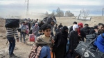 This photo released by the Syrian official news agency SANA, shows Syrian civilians with their belongings, fleeing from fighting between the Syrian government forces and rebels, in Hamouria in eastern Ghouta, a suburb of Damascus, Syria, Thursday, March. 15, 2018. (SANA via AP)