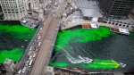 A boat moves through the water as the Chicago River is dyed green for St. Patrick's Day Saturday, March 17, 2018, in Chicago. Thousands of people lined the riverfront downtown Chicago to see the dyeing, a tradition for the holiday that dates to 1962. (Erin Hooley/Chicago Tribune via AP)