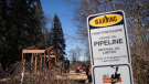 "A sign warms of an underground pipeline as people construct a ""watch house"" near a gate leading to Kinder Morgan's property in this March 10, 2018 file image. (THE CANADIAN PRESS/Darryl Dyck)"