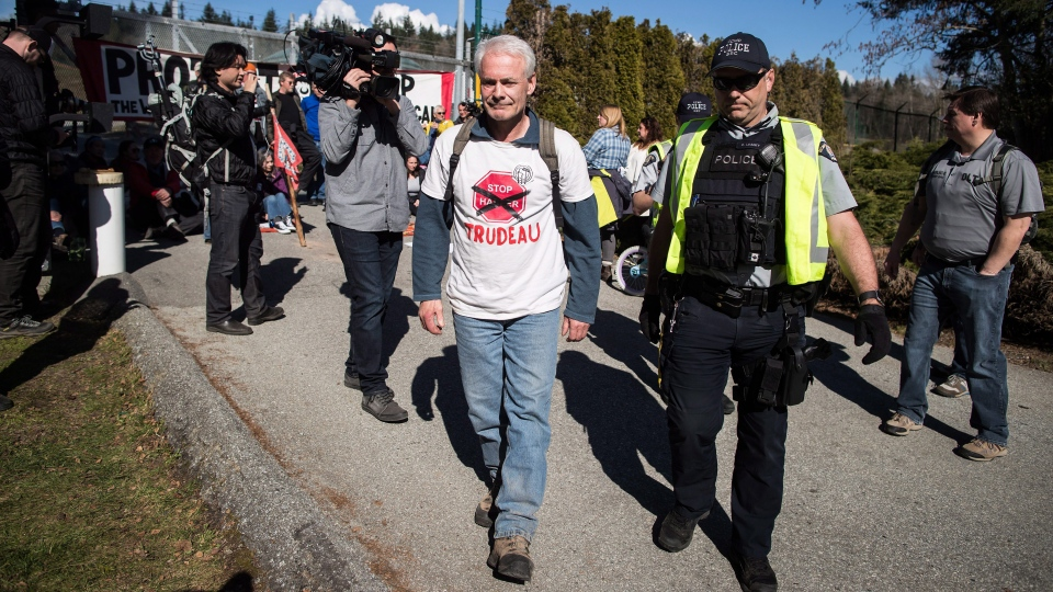 An RCMP officer arrests a protester outside Kinder Morgan in Burnaby, B.C., on Saturday March 17, 2018. (THE CANADIAN PRESS / Darryl Dyck)