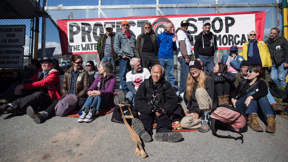 Protesters block a gate outside Kinder Morgan before RCMP officers moved in and arrested them for defying a court order, in Burnaby, B.C., on Saturday March 17, 2018. (THE CANADIAN PRESS/Darryl Dyck)