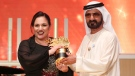 British school teacher Andria Zafirakou, left accepts the Global Teacher Prize trophy from Dubai's ruler, Sheikh Mohammed bin Rashid Al Maktoum, at a ceremony in Dubai, United Arab Emirates, Sunday, March 18, 2018.  (AP Photo/Jon Gambrell)