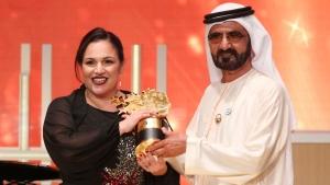 British school teacher Andria Zafirakou, left accepts the Global Teacher Prize trophy from Dubai's ruler, Sheikh Mohammed bin Rashid Al Maktoum, at a ceremony in Dubai, United Arab Emirates, Sunday, March 18, 2018.  (AP Photo/Jon Gambrell)