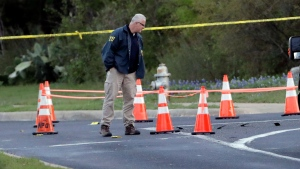 Officials work near the site of Sunday's deadly explosion, Monday, March 19, 2018, in Austin, Texas. Police warned nearby residents to remain indoors overnight as investigators looked for possible links to other package bombings elsewhere in the city this month. (AP Photo/Eric Gay)