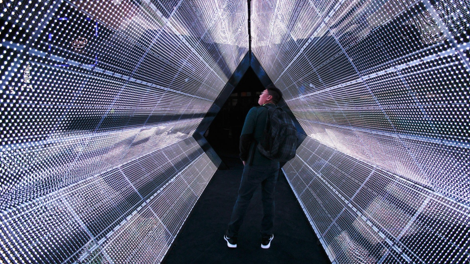 In this Tuesday, Jan. 9, 2018, file photo, a man stands in the 5G tunnel at the Intel booth at CES International in Las Vegas. (AP Photo/Jae C. Hong, File)