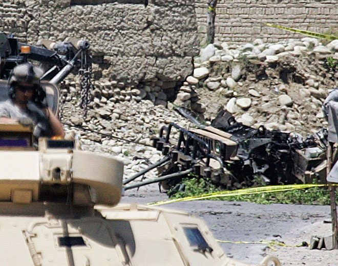 A U.S. soldier stands guard on the top of an armored vehicle near the site of an explosion in Kapisa province north of Kabul, Afghanistan, Tuesday, May 26, 2009. (AP / Rafiq Maqbool)
