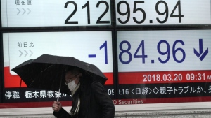 A man walks past an electronic stock board showing Japan's Nikkei 225 index at a securities firm in Tokyo Tuesday, March 20, 2018. (AP Photo/Eugene Hoshiko)