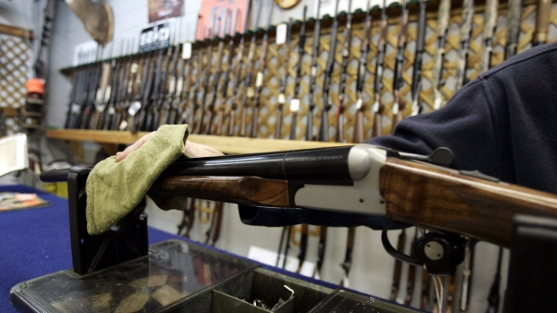 A Ottawa hunting store salesperson wipes a shotgun on Tuesday, May 16, 2006. THE CANADIAN PRESS/Jonathan Hayward