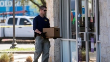 An FBI official carries items into a FedEX Office store Tuesday, March 20, 2018, in the southwest Austin suburb of Sunset Valley, Texas, as authorities investigate a recent string of package bombs. (Reshma Kirpalani/Austin American-Statesman via AP)