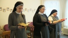 Sister Gemma MacLeod, middle, is seen with a book in her hands.