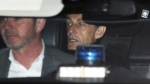 Former French President Nicolas Sarkozy, right, leaves the police station where he was held, in Nanterre, outside Paris, on March 21, 2018. (Francois Mori / AP)