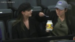 Two women share a jar of mayonnaise at an NBA game